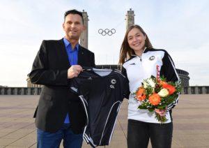 Heißt Gina Lückenkemper in Berlin willkommen: SCC-Geschäftsführer Andreas Hilmer überreicht Sprint-Ass Gina Lückenkemper vor dem Olympiastadion das Vereinstrikot (Foto: SCC Berlin/Camera 4)